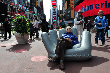 entertainment industry: NY - OCT 08:Tourist sit on a giant baseball glove in Time Square on October 08 2010 in Manhattan New York, USA.Its a major center of the worlds entertainment industry.