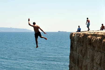 acre: ACRE, ISR - MAY 13:Young Arab men jumps from the top of the ancient sea walls of Acre on May 13 2009.Acre is one of the oldest continuously inhabited sites in Israel.