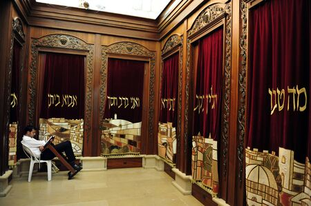 mishnah: JERUSALEM - JULY 30: An Israeli Jewish orthodox man prays in a synagogue, reads a torah book (siddur) and wears, tefillin, tzitzit and tallit on July 30 2009 in Jerusalem, Israel.
