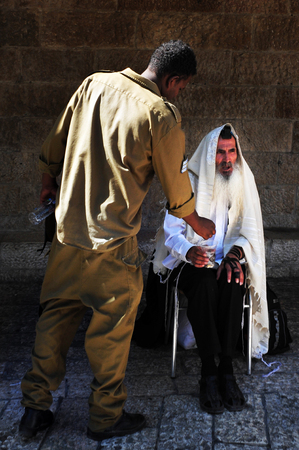 mishnah: JERUSALEM - JULY 30: An Israeli soldier gives charity tzedakah to an old Jewish orthodox man in the street on July 30 2009 in Jerusalem, Israel. Unlike philanthropy or charity, tzedakah is seen as a religious obligation, which must be performed regardless