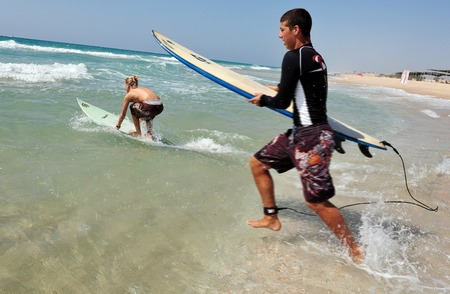 discovered: ASHDOD - JULY 19:Two wave surfers run to the sea on July 19 2009 in Ashdod, Israel.It originated by Polynesian people and was first discovered by Captain Cook in 1778. .