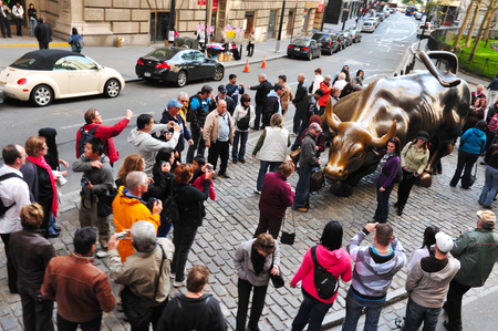 charging bull: NY - OCT 09:Tourists visits the Wall Street Charging Bull statue in Wall Street Manhattan New York.Its the symbol of aggressive financial optimism and prosperity. Editorial