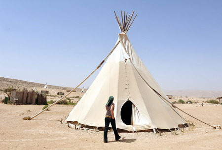 plains indian: NEGEV,ISR - FEB 15:Woman live in Tipi on February 15 2011.Painted  plains Indians tipis were mainly featured geometric portrayals of celestial bodies, war battles and animal designs.