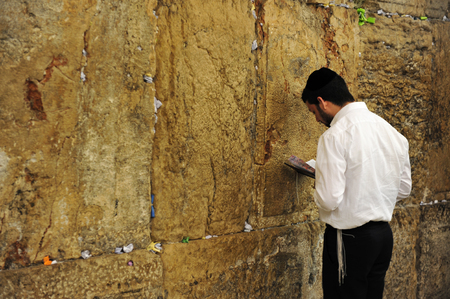 remnant: JERUSALEM -JULY 30: Jewish man is praying at the western wall on July 30 2009 in Jerusalem, Israel.It is a remnant of the ancient wall that surrounded the Jewish Temples and is the most sacred site recognized by the Jewish faith outside of the Temple Mou
