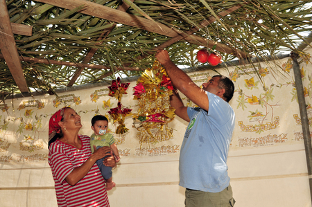 succos: NETIVOT - OCTOBER 02: Israeli Jewish family decorates their Sukkah on the eve of the Jewish holiday Sukkoth on October 02, 2009 in Netivot, Israel.