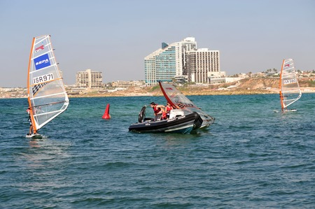 olympic sports: HERZLIYA,ISR- OCT 06:Israeli youth learn to wind surf along Herzliya Pituah skyline on Oct 06 2009.Windsurfing is one of Israels most successful olympic sports.