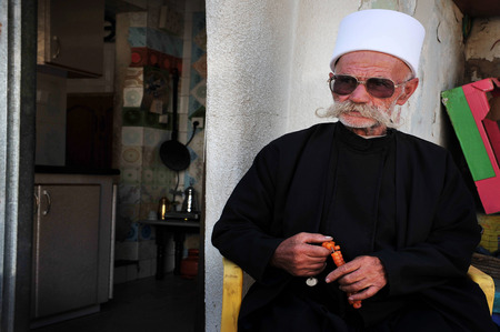 exceeds: MAJDAL SHAMS - AUGUST 23:A Druze man sit outside his front door in Majdal Shams,Israel on August 23 2009.The number of Druze people worldwide exceeds one million, with the vast majority residing in the Middle East.