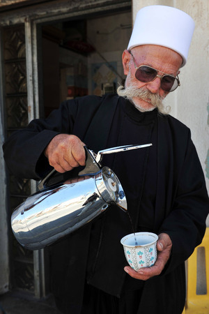monotheism: MAJDAL SHAMS - AUGUST 23:Israeli Druze man is pouring coffee in Majdal Shams, Israel on August 23 2009.The number of Druze people worldwide exceeds one million, with the vast majority residing in the Middle East. Editorial