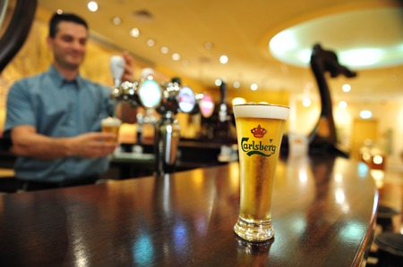 carlsberg: ASHKELON - JULY 27: A man bartender pours a glass of Carlsberg beer at a pub in the Israeli Beer Breweries (IBBL) on July 27 2009 in Ashkelon, Israel. Editorial