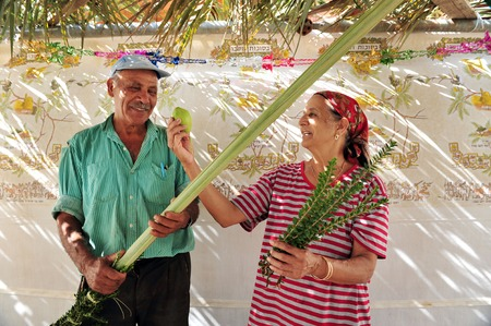 sukkoth: NETIVOT - OCTOBER 02: An old Israeli Jewish couple holds the Four Species in their Sukkah on the eve of the Jewish holiday Sukkoth on October 02, 2009 in Netivot, Israel. Editorial