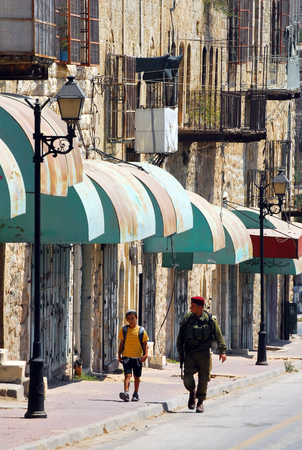 jewish community: HEBRON, ISRAEL - SEP 08:Israeli soldier gourds on the Jewish quarter of Hebron on September 09 2009.Hebron is the site of the oldest Jewish community in the world, which dates back to Biblical times.