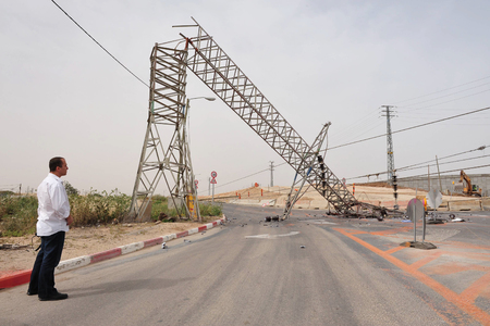 toppled: KIRYAT GAT, ISR - MAY 04:Man looks at toppled overhead power line on April 04 2009.High voltage transmission lines carry a lot of energy or power and if not treated with respect can be fatal Editorial