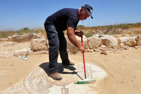 gat: AMATZIA, ISR - AUG 02:Archaeologist expose a Mosaic at Amatzia Caves near Kiryat Gat on August 02 2009.During troubled times, the Jews of ancient Israel often dwelled in artificial limestone underground caves.