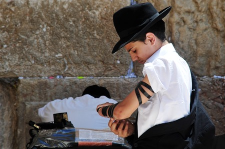 hassid: JERUSALEM  - JULY 28:Jewish Man wrapped in tefillin pray at the Western Wall on July 28 2009 in Jerusalem, Israel..Its the most sacred site by the Jewish faith outside of the Temple Mount itself.