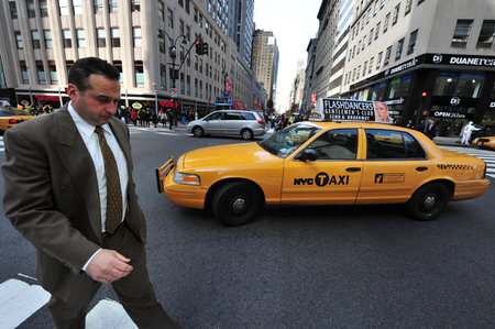 taxicabs: NY - OCT 09: Caucasian businessman beside a yellow taxicab on October 09 2009 in Manhattan New York.Over a million people ride a cab every day Editorial