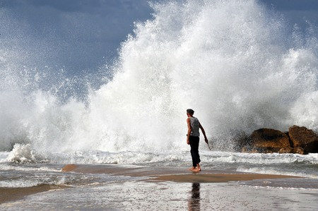 end times: ASHKELON - NOV 02:Israeli man walk into a giant wave on Nov 02 2009.According to a recent research about consequences of rising sea levels, a six-meter tsunami waves can strikes Israels coast.