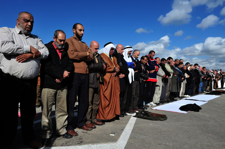 EREZ CROSSING - DECEMBER 31:A large group of Muslim Palestinian Arabs pray to Allah during a protest in Erez crossing on December 31 2009.According to Islamic belief, Allah is the proper name of God and humble submission to His Will, Divine Ordinances and Editorial