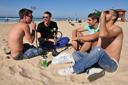 minors: ASHDOD, ISR - JAN 16:Young Israeli men smoke and drink alcohol on January 16 2010.The Israeli law prohibits selling or serving alcohol to minors, however the law does not prohibit minors to drink. Editorial