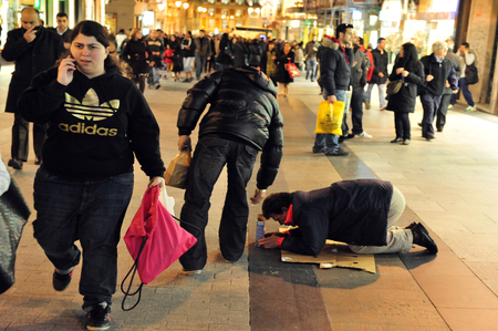wellfare: MADRID - MAR 01:Beggar in Calle Arenal street at night on March 01 2010  in Madrid,Spain.Today, 25% of Spanish workers are unemployed and a growing number of them cant afford to buy enough food to live. Editorial