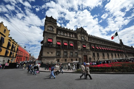 MEXICO CITY - FEB 23:Mexican people walk near the National Palace on February 23 2010 in Mexico City, Mexico.was commissioned and designed by Hernan Cortez, and is one of the oldest buildings in Mexico City. Editorial