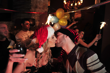 good wishes: ASHDOD, ISR - JAN 01:Couple is kissing to welcome the new years on Jan 01 2010.Many people see the old year out in party,toasts of champagne and exchanging good wishes for a Happy New Year. Editorial