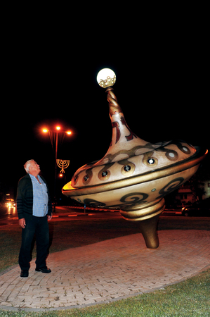 chanukiah: ASHKELON - DECEMBER 1: A man is standing near the biggest savivon (dradle or spinning top) in Israel, about 5 meters high which is also used as an 8 candle menorah (candelabra) to celebrate the Jewish holiday of Hanukkah in Ashkelon, Israel on Wednesday D