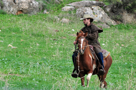 east riding: GOLAN HEIGHTS - DECEMBER 13:Israeli cowboy rids his horse in the Golan Heights, Israel on December 13 2009. About 18,000 Israeli settlers have moved to the Golan, which also borders Jordan, since 1967