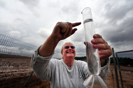weather gauge: NEGBA, ISR - OCT 30:Smiling and happy Meteorologist measure water level in a rain gauges on Oct 30 2009.The first known rainfall records were kept by the Ancient Greeks, about 500 B.C. Editorial