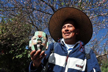 indian artifacts: TEOTIHUCAN - FEB 26:Mexican man selling a replica mask of ancient Aztec on February 26 2010 in Teotihuacan, Mexico.Ancient Aztec art was traded, and much of the materials used were imported.