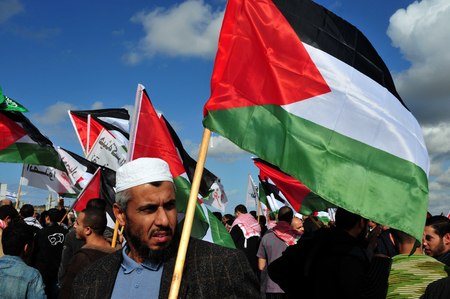 anti war: EREZ CROSSING - DECEMBER 31:A large group of Palestinian Arabs carry Palestinian flags during a protest on the Gaza-Israel border on December 31 2009.The entire  Palestinian population in Gaza Strip is 1.6 million people. Editorial