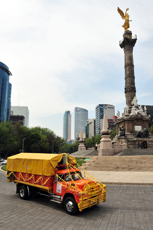 paseo: MEXICO CITY - FEB 24: Mexican yellow truck passing under the Angel de la Independencia  on February 24 210 in Mexico City, Mexico.Its one of the most recognizable landmarks in Mexico City