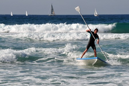 ashdod: ASHDOD - JAN 16: A man rids a Hasake on January 16 2010 in Ashdod,Israel. Its Israeli SUP Surfing board dating back to the 8th century A.D.