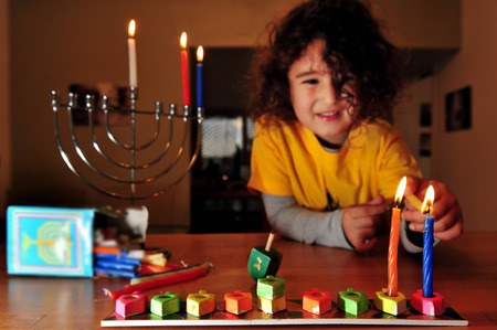 chanukkah: Jewish girl is lighting the secound candles for the Jewish holiday of Hanukkah. Hanukkah or Chanukah, Chanukkah, or Chanuka, also known as the Festival of Lights, is an eight-day Jewish holiday. Hanukkah is observed for eight nights and days. Editorial
