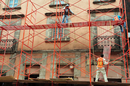 originated: MEXICO CITY - FEB 23:Mexican workers works on scaffolding construction on Febauary 23 2010 in Mexico City, Mexico.Scaffolding originated in ancient North Africa and China.
