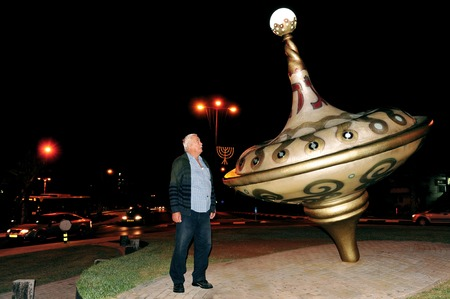 hanukiah: ASHKELON - DECEMBER 1: A man is standing near the biggest savivon (dradle or spinning top) in Israel, about 5 meters high which is also used as an 8 candle menorah (candelabra) to celebrate the Jewish holiday of Hanukkah in Ashkelon, Israel on Wednesday D