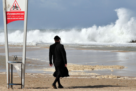 end times: ASHKELON - NOV 02:Jewish orthodox looks at giant waves on Nov 02 2009.According to a recent research about consequences of rising sea levels, a six-meter tsunami waves can strikes Israels coast. Editorial