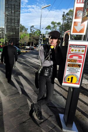 payphone: MEXICO CITY - FEB 24:Young Mexican man talking on a pay phone on February 24 2010 in Mexico City, Mexico.In Mexico today the demand for pay phone usage has virtually collapsed.