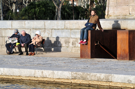 spanish looking: MADRID - MARCH 01:Spanish people enjoy the warm sun in a park on March 01 2010 in Madrid, Spain.The population of Madrid was 950 000 in 1900 now it is over 3 million.