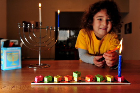 chanuka: Jewish girl is lighting the first candle for the Jewish holiday of Hanukkah. Hanukkah or Chanukah, Chanukkah, or Chanuka, also known as the Festival of Lights, is an eight-day Jewish holiday. Hanukkah is observed for eight nights and days.