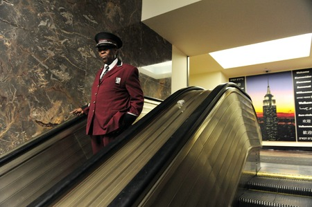 famous industries: NY - OCT 11: Hotel bellboy coming down in the escalator of the Empire State Building on October 11 2009 in Manhattan, New York.It was the first building in the world to have more than 100 floors. Editorial