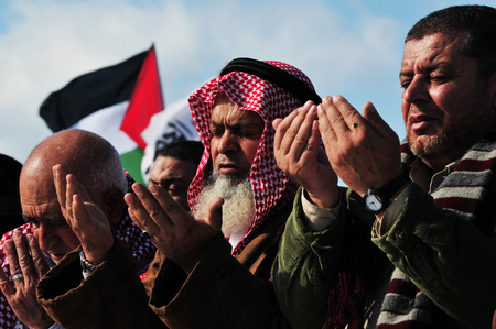 ordinances: EREZ CROSSING - DECEMBER 31:A large group of Muslim Palestinian Arabs pray to Allah during a protest in Erez crossing on December 31 2009.According to Islamic belief, Allah is the proper name of God and humble submission to His Will, Divine Ordinances and Editorial