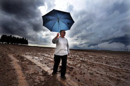 precipitaci�n: Negba, ISR - DIC 30: La persona sostiene el paraguas en el campo durante la tormenta el 30 oct 2009. El promedio de precipitaci�n anual global de la tierra es de 715 mil�metros (28,1 pulgadas).
