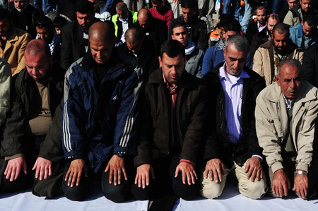 spiritualism: EREZ CROSSING - DECEMBER 31:A large group of Muslim Palestinian Arabs pray to Allah during a protest in Erez crossing on December 31 2009.According to Islamic belief, Allah is the proper name of God and humble submission to His Will, Divine Ordinances and Editorial