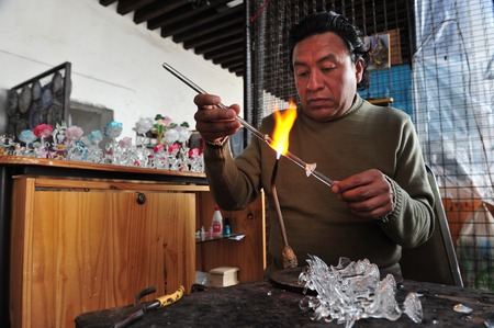 phoenicians: PUEBLA - FEB 25:Mexican Glass blower at the Artist Market on Feb 25 2010 in Puebla City, Mexico.is a glass forming technique which was invented by the Phoenicians around 50 BC