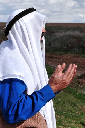WESTERN NEGEV - DECEMBER 31:A Muslim Palestinian Arab man pray to Allah in the Western Negev on December 31 2009.According to Islamic belief, Allah is the proper name of God and humble submission to His Will, Divine Ordinances and Commandments is the pivo