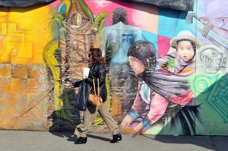 urban colors: CIUDAD DE MÉXICO - 25 de febrero: Mujer mexicana pasando por una calle de arte-graffiti el 25 de febrero en la ciudad de México, Mexico.Graffiti se encontró por primera vez en la antigua arquitectura romana.
