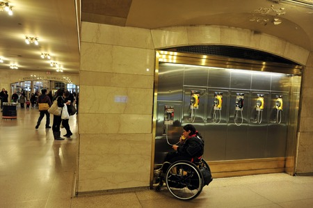payphone: NY - OCT 14:Disabled man sit on a wheelchair and talks on a pay phoneat the Grand Central Station Manhattan on October 14 2009 in Manhattan New York, USA.Grand Central Terminal turns 100 in 2013