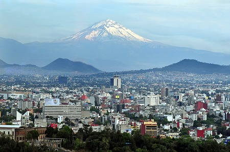 MEXICO CITY - MAR 01 2010:Aerial landscape view of the Popocatepetl volcano mountain rais above Mexico city.The city surrounded by mountains and volcanoes that reach elevations of over 5,000 meters.