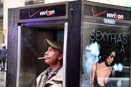 plazas: NY - OCT 15:New Yorker smokes cigarette insid a Payphone box on October 15 2009 in Manhattan New York, USA.Today all public parks, beaches and pedestrian plazas are smoke-free, enforced by a $50 fine. Editorial