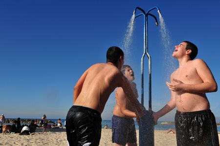ashdod: ASHDOD - JAN 09:Young Israeli man cools down under beach water shower on Jan 09 2010.The highest recorded temperatures in Israel was 129 Fahrenheit Degrees (54 Celsius) in Tirat Tsvi on June 21 1942.